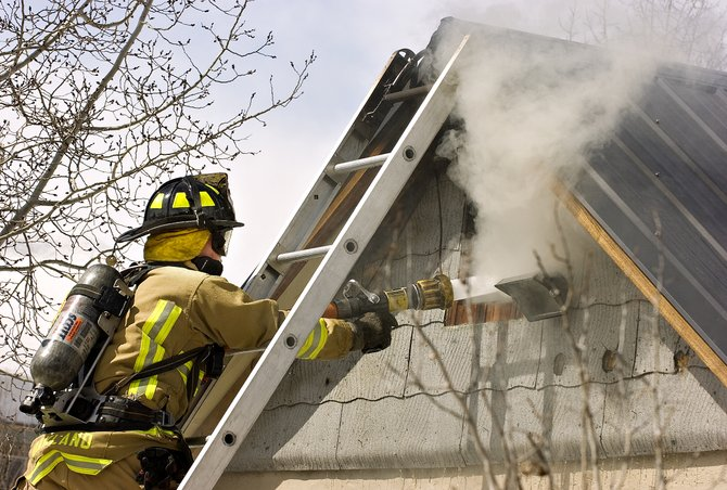 Steamboat Springs Fire Rescue firefighter Joe Oakland directs a stream of water at a fire in the attic of the home at 43 Logan Ave. in Steamboat Springs on Wednesday afternoon.