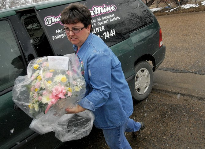 Shirley Balleck gets out of her van Thursday to deliver flowers to a residential house. Balleck has owned The Flower Mine & Gift Shop for three years and maintains a delivery schedule, as well.
