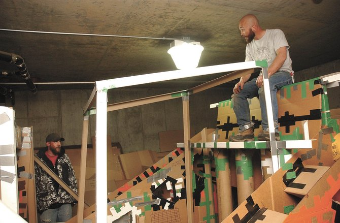 Lead builders Jim Fletcher, right, and Carl Reichenbach discuss the construction of their Cardboard Classic craft Thursday in an underground parking garage. Race day is Saturday.
