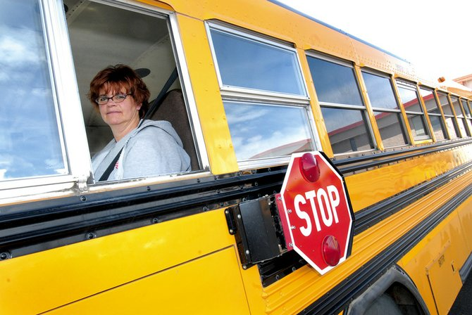Valerie Pfifer leans out of the window of her bus Wednesday while waiting to pick up students at Ridgeview Elementary School. Pfifer has been driving MCHS athletes for 26 years.