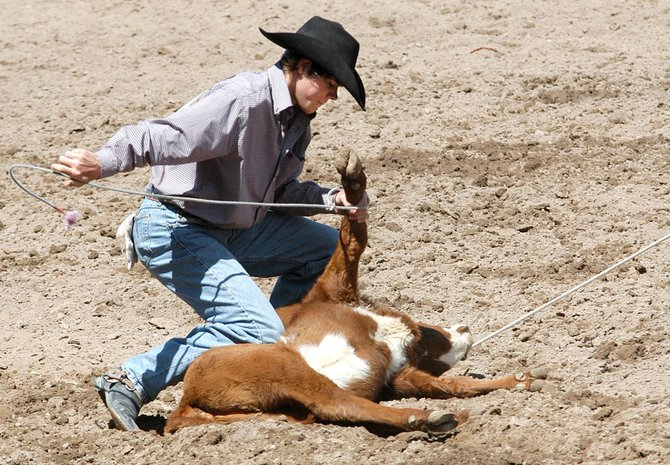 Eric Fleming ties off a calf during the calf-roping portion of last year's Moffat County High School rodeo. The MCHS rodeo team kicked off its season Saturday in Cortez.