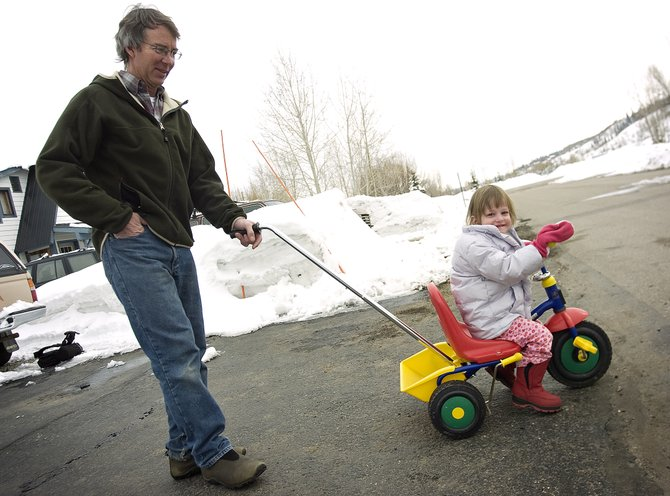 Jim Engelken, left, and his daughter Elisa play outside their house on Pamela Lane in Steamboat Springs on Tuesday afternoon. Engelken strongly opposes Triple Crown's proposed use of the Emerald Park fields because of the increased traffic that would occur on Pamela Lane, which leads to the park.