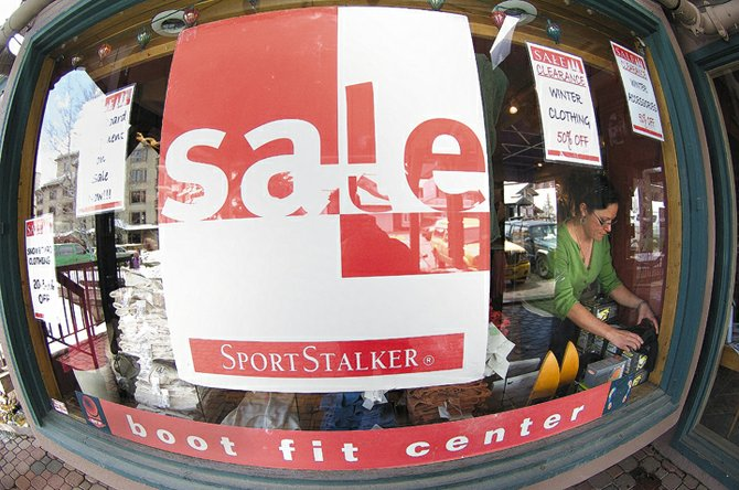 Powder Divas employee Hilary Thissen straightens sale items in the window of the Ski Time Square business. The store is scheduled to close for the season Sunday but is offering plenty of good deals to customers during the final days of the season.