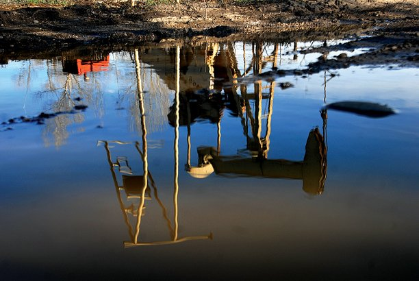 An oil rig is reflected in a puddle of water near the Yampa Valley Golf Course.
