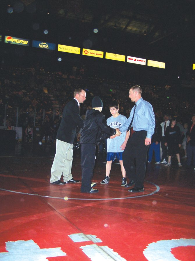 Hayden Middle School Wrestling coach Dallas Robinson and T-Lane Mazzola, left, greet Emilio Martinez and his coach from Valley before their championship match at the inaugural Colorado Middle School Championships on Saturday at the Budweiser Event Center in Loveland. Mazzola lost, 10-4, to the three-time national champion.
