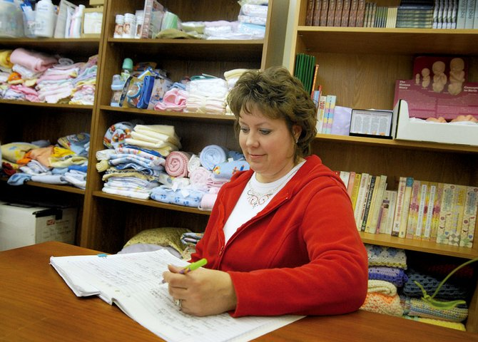 Debbie Rudd, Yampa Valley Pregnancy Center director, sits with a notebook and one of the pens she bought hours after the Country Mall fire that destroyed the center's office. She bought the notebook because she knew she would need to record a lot of phone numbers and the pens - which feature pictures of Winnie the Pooh - because she knew she would need a smile, she said.