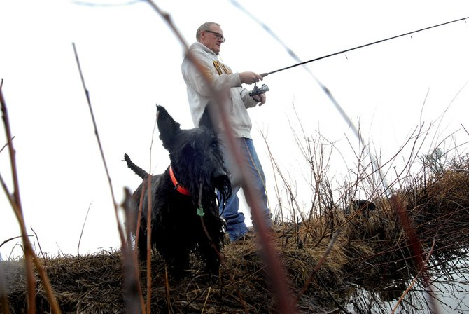 Joe Foy gets some fishing in with his dogs Mollie and Shortie, not pictured, Wednesday at Loudy-Simpson Park during a break in the rainy weather.