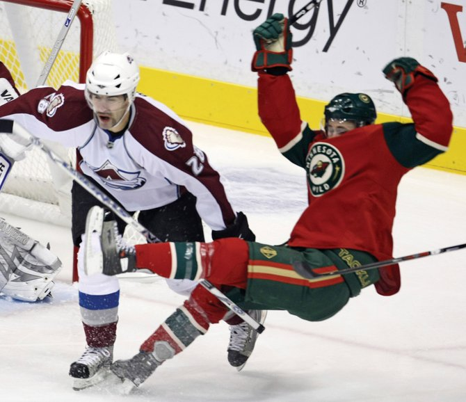 The Colorado Avalanche's Ben Guite, left, trips the Minnesota Wild's Pierre-Marc Bouchard in the first period of Game 1 of the first round of the Stanley Cup playoffs at the Xcel Energy Center in St. Paul, Minn., on Wednesday. The Avalanche won in overtime, 3-2.