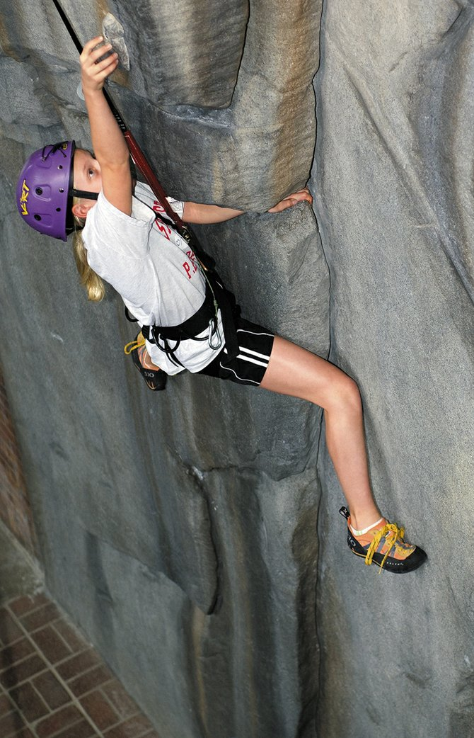 Malia Fraioli reaches for a hold while making her way up the new climbing wall at Steamboat Springs Middle School. The wall was built through a fundraising effort of more than $30,000 led by Everything Outdoor Steamboat and teacher Matt Tredway. Malia is in Tredway's sixth-grade fitness class.