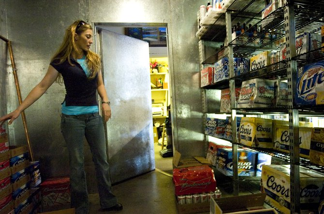 Brooke Cape works to restock the shelves in the beer cooler at Southside Liquors in Steamboat Springs on Friday afternoon. Local businesses are less than thrilled about legislation allowing Sunday sales that Gov. Bill Ritter is schedule to sign Monday.