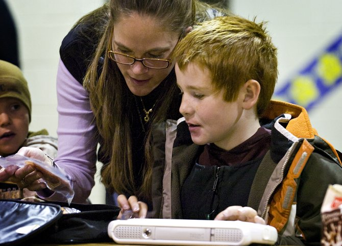 Severe Needs Paraprofessional Heidi Mueller uses a Tango assistive technology device to communicate with first-grader Jack English during lunchtime at Strawberry Park Elementary School on Friday.