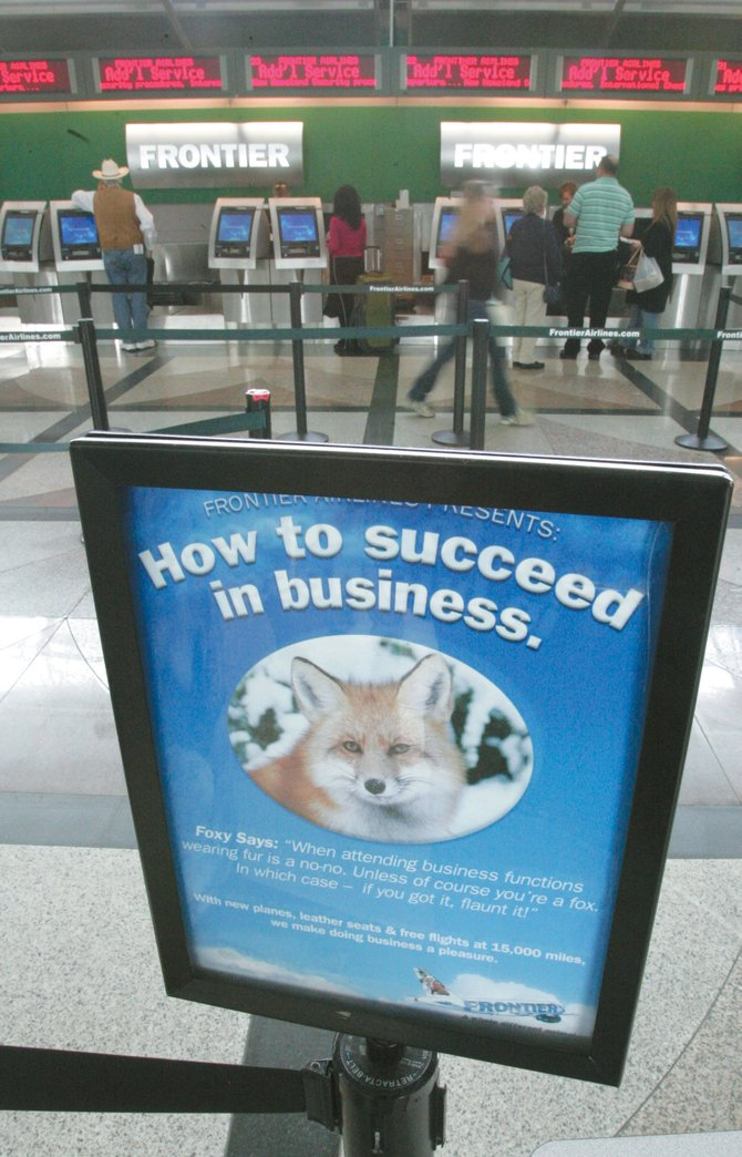 A marketing sign for Frontier Airlines stands in front of the ticket counter at Denver International Airport on Wednesday, hours after Frontier filed for Chapter 11 bankruptcy. Frontier says operations will continue as usual, and flights will not be affected.
