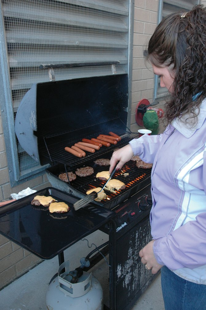 Routt County Communications dispatcher Leslie Hockaday slides burgers off the grill at a cookout honoring the people who handle all of Routt County's emergency calls. The event lined up with National Public Safety Telecommunications Week.