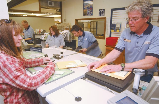 North Routt County resident Tonja Coates works with United States Postal Service clerk Ken Gibbon to mail taxes Monday at the post office, 200 Lincoln Ave. The post office is anticipating a steady stream of last-minute tax filers today.  The main Steamboat post office closes at 5 p.m. today, its usual time.