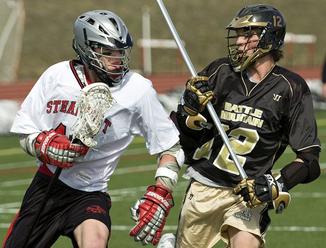 Steamboat's Tyler Ostrom, left, makes contact with a Battle Mountain defender during the game at Gardner Field in Steamboat Springs on Tuesday afternoon. Steamboat defeated Battle Mountain, 12-6.