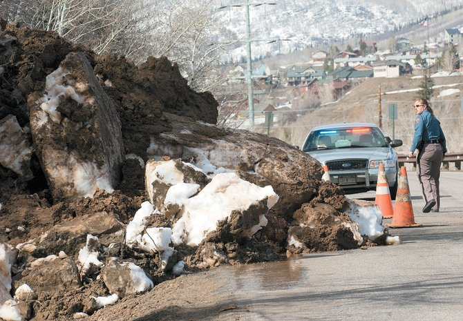 State trooper Melissa Fowler places cones in front of a mudslide that shut down County Road 14 thee-tenths of a mile north of the intersection of CR14 and Mt. Werner Road. The road will be closed for repairs between Treehaus and Brooklyn neighborhood until 6 p.m. on April 18.