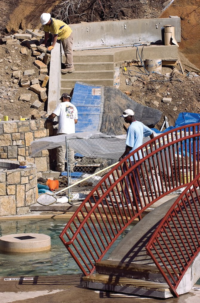 Construction crews work to complete the stonework and other projects near the hot springs pools at Old Town Hot Springs in downtown Steamboat Springs on Tuesday afternoon. The Hot Springs Board of Directors voted last week to defer the new construction fee and seek other ways to raise money for the next phase of construction, which may include expansion of the fitness portion of the recreation center.