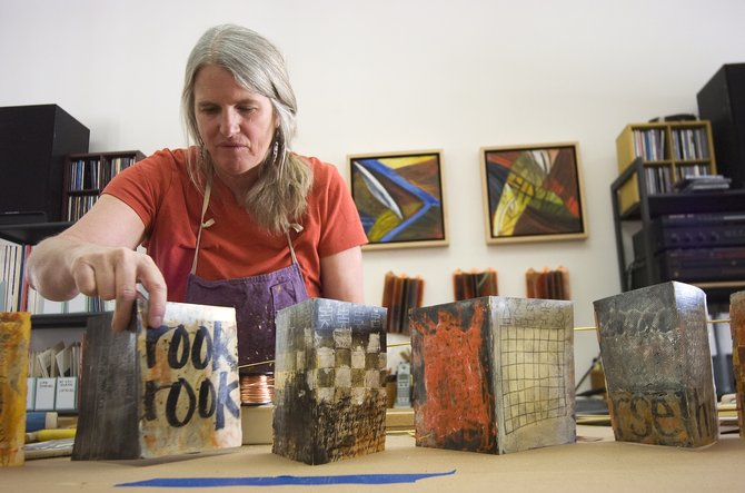 Laura Wait arranges pages on a frame in her Steamboat Springs studio. The work is part of a new book art series centered on chess.