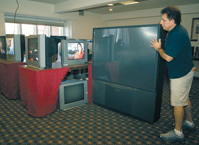 Edgar Castellon, of National Content Liquidators, moves a big screen television into the sample room at the Thunderhead Lodge on Tuesday afternoon. The items from the longtime Steamboat Springs hotel will be sold starting this Thursday during a 30-day liquidation sale.
