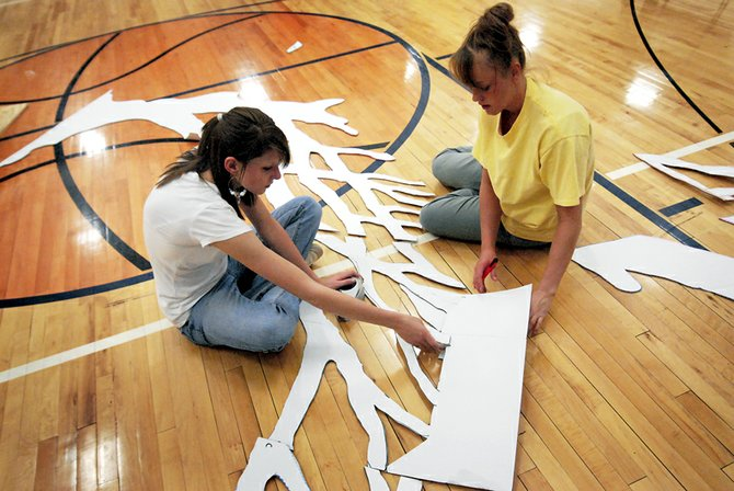 "Danette Crofts, left, and Dani Kawcak work on the set Tuesday in preparation for the Moffat County High School prom Saturday night. The theme this year is ""Once Upon A Dream."""