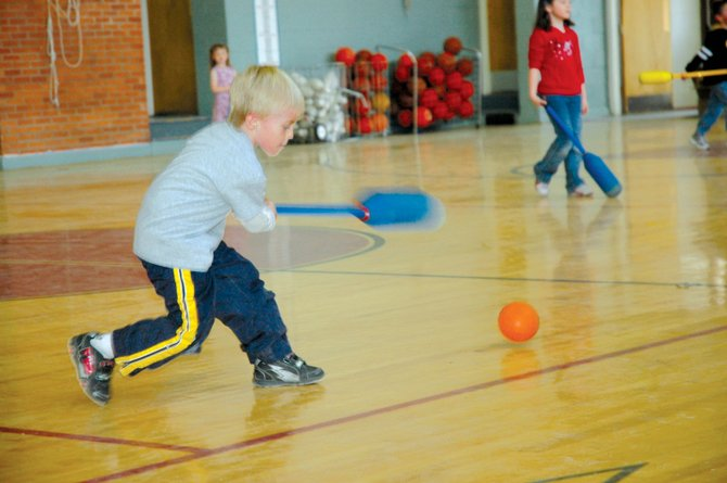 Kindergartener Nick Estes takes a swing Thursday while playing broomball at South Routt Elementary School in Yampa. The school's gym has new infrared lights hanging from the ceiling, part of a $4.1 million overhaul to improve energy efficiency in South Routt schools. Hung about two weeks ago, the new lights noticeably brighten up the gym.