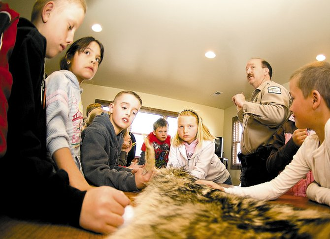Senior Park Ranger Ed Keleher speaks to a group of Hayden Elementary School students on Thursday at the Yampa River State Park during a field trip.  The students were looking at fur from a coyote and listening to Keleher's descriptions of the animal and its role in the local ecosystem.
