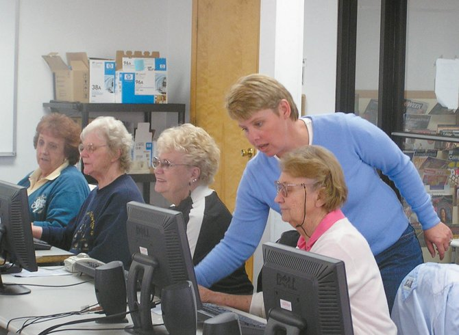 Assistant instructor Melissa George helps students in the Senior Computer Basics class at CNCC. The class, new this year, will be offered again this summer.