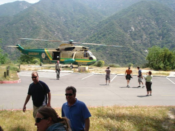 Wedding guests of Steamboat couple Ken Grady and Julie Grady (formerly Sokolowski) walk away from the helicopter that airlifted them out of the remote California camp where the couple's wedding was held. A wildfire in the mountains northeast of Los Angeles forced the evacuation of the wedding celebration.