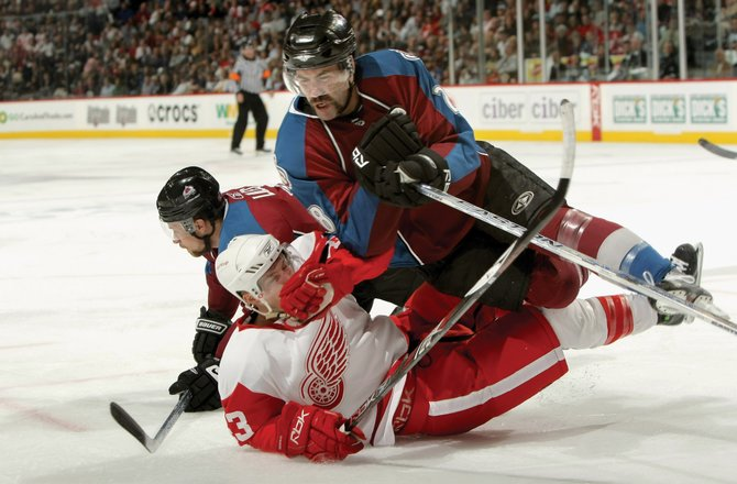 Ben Guite of the Colorado Avalanche checks Darren Helm of the Detroit Red Wings after Helm checked John-Michael Liles of the Avalanche during Game 4 of the Western Conference Semifinals of the 2008 NHL Stanley Cup Playoffs on Thursday at the Pepsi Center. The Avs lost, 8-2.