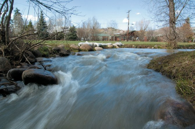 The fast-moving waters of Butcherknife Creek already are pushing the river banks, notice the sandbags at the curve of the creek, as it runs through Stehley Park near downtown Steamboat Springs. Officials warn that the water will continue to rise as snow begins to melt off the higher peaks around Steamboat Springs.