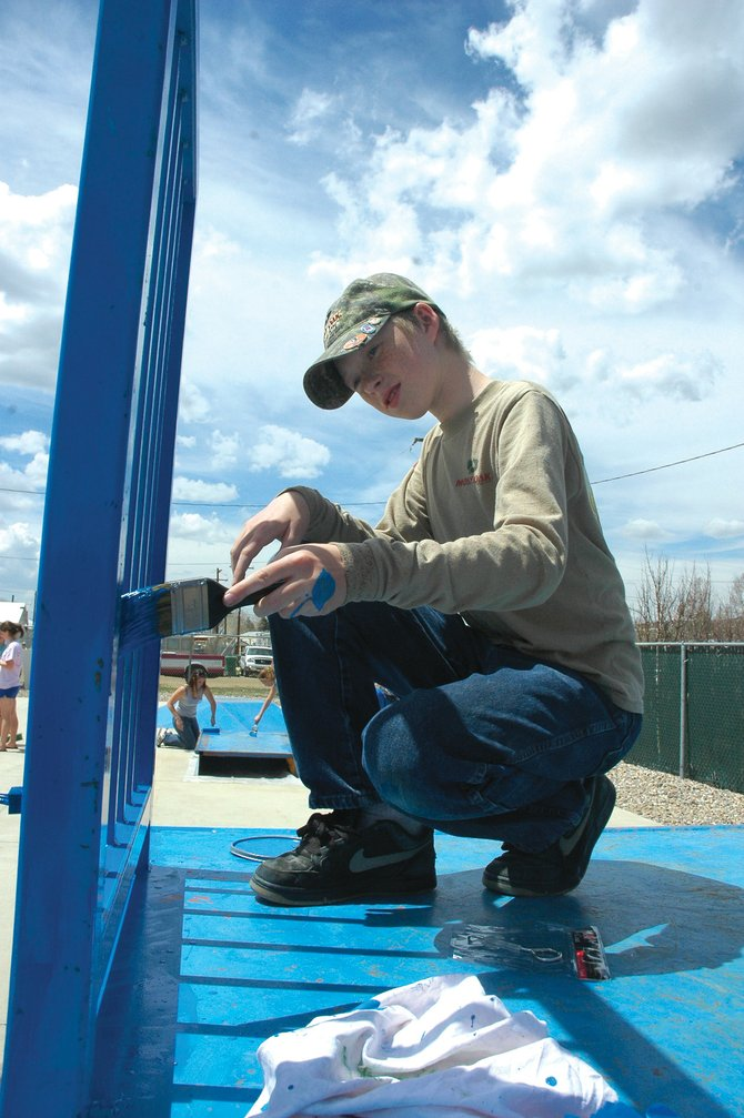 Hayden Middle School seventh-grader Cole Miller, 13, paints a railing on the top of a skatepark ramp Wednesday in Hayden. Nearly 100 middle school students participated in projects across town as part of Global Youth Service Day.