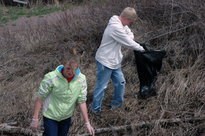 Eighth-graders Lindsay Miles and Brandon Leu hunt for trash along Colorado Highway 131 on Thursday in Oak Creek, where Soroco Middle School students participated in National and Global  Youth Service Day.