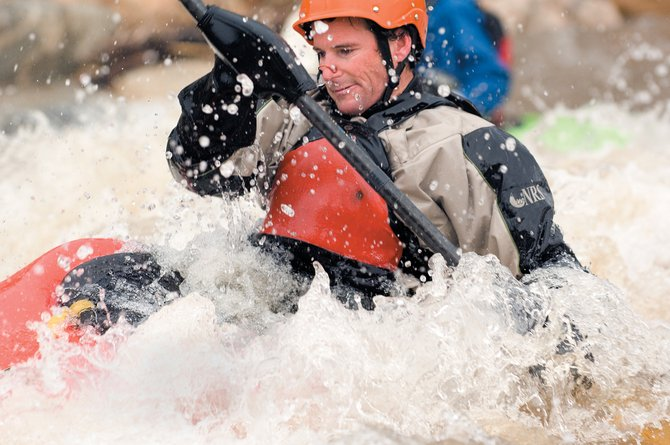 The roller waters of the Yampa River surround kayaker Eugene Buchanan last week in Charley's Hole. Record snow has put smiles on the faces of local kayakers eager to spend their afternoons challenging the fast-moving waters.