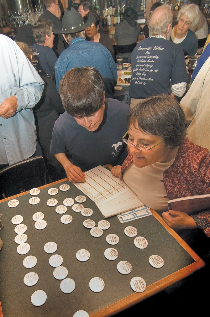 Catherine Carson, chairwoman of the Routt County Democratic Party, and delegate Joanna Erickson go through buttons at a democratic gathering at Mahogany Ridge Brewery & Grill last week.