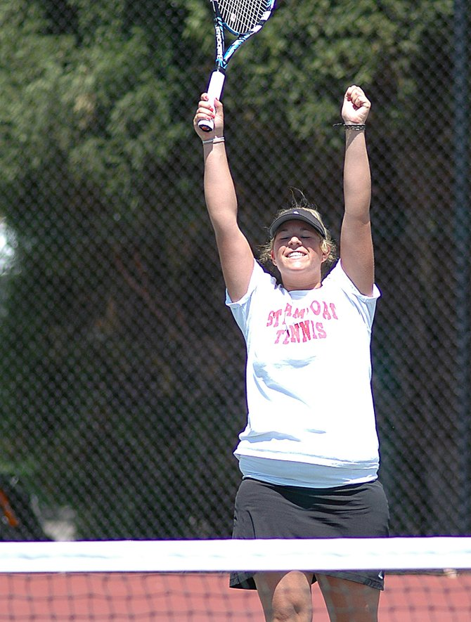 Molly Weiss raises her arms in celebration Saturday after scoring the winning point in the No. 3 singles state championship match. Weiss had a 5-2 lead in the final set but nearly gave it all back, winning the set, 6-4.