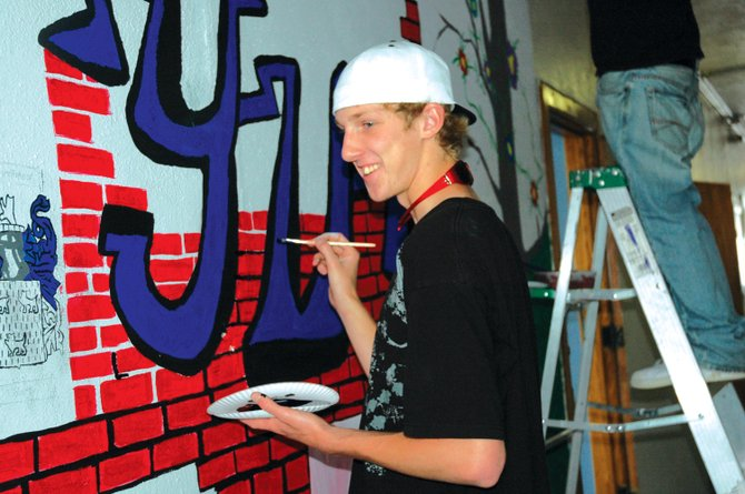 "Robert Anderson, 17, chats with a classmate Thursday while painting the letters ""YVS,"" for Yampa Valley School, on a mural outside the school's classroom. Anderson lives in Yampa but said the daily commute to Steamboat Springs is well worth it because Yampa Valley School is helping him catch up on credits after missing about two years of high school."