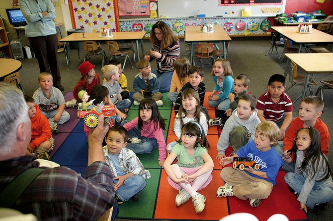 Lou Wyman, left, shows Sunset Elementary School kindergarten students an old time tin toy May 1 at the school. Stories from the kindergartners and other Sunset Elementary students will be featured in a book that is scheduled for completion this week.