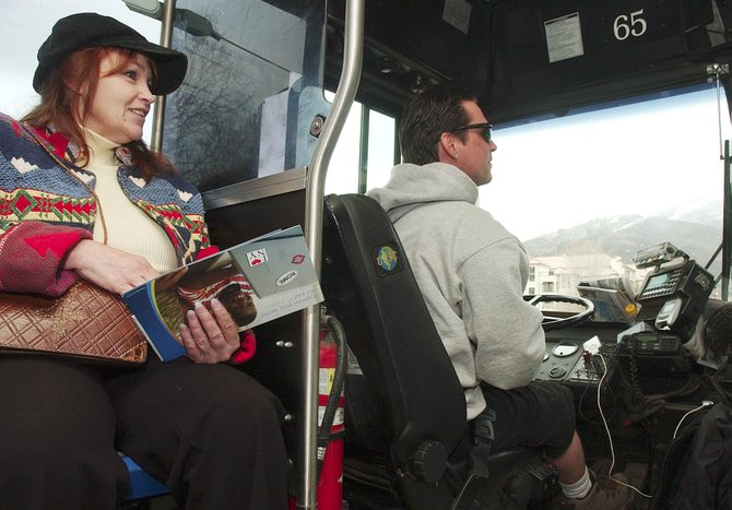 Bus passenger Lisa Swink talks with Steamboat Springs Transit driver Chris Gray on Thursday while riding the bus to the south side of town. With high gasoline prices, some Routt County residents are changing their routines to use public transit.