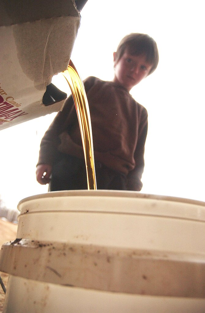 Mason Voyvodic watches as his father, Chris Voyvodic, pours used vegetable oil into a bucket at their home. After filtering the oil, which he salvages from Mazzola's Italian Restaurant, he is able to use it to power his diesel truck.