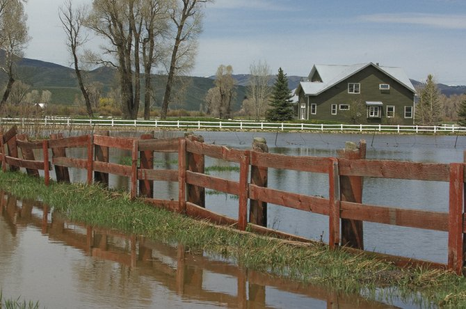 The rising waters near the confluence of the Elk and Yampa rivers surround a house near Routt County Road 44 west of Steamboat Springs. Homeowners are using sandbags and building berms to keep the rising waters away from property and the road.
