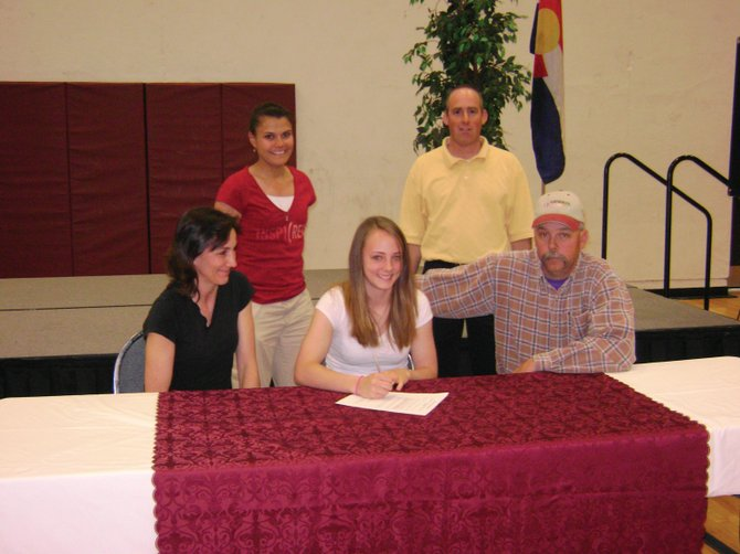 Kelsey Samuelson, with her mom Alicia on her left and dad Greg on her right, signs a letter of intent to play basketball at Colorado Northwestern Community College in Rangely. Samuelson's coach Danelle Rivera, top left, and athletics director Andy Johnson look on.