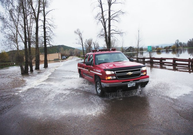 Steamboat Springs Assistant Fire Chief Bob Struble drives his truck Thursday morning through a water-covered section of Routt County Road 44 where it intersects U.S. Highway 40 west of Steamboat Springs.