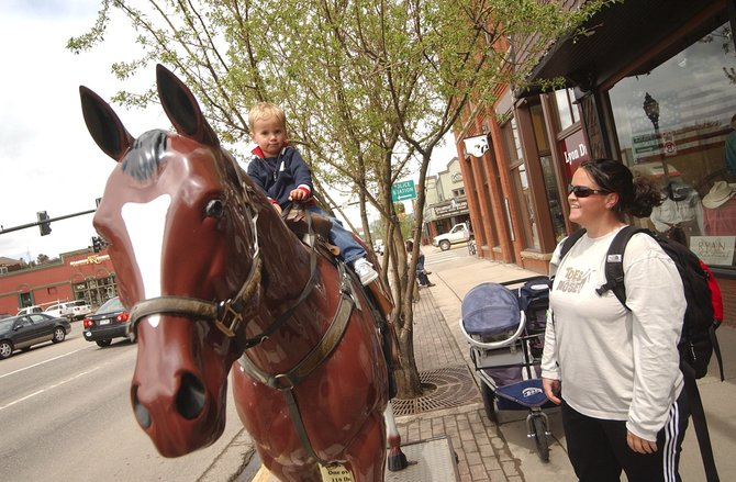 Karen Strong watches her 2-year-old son, Kyan, ride Lightning on Friday in front of F.M. Light & Sons. Britina Design Group is in the process of developing a Downtown Streetscape Improvement Plan, which would address pedestrian, bicycle and vehicle improvements.