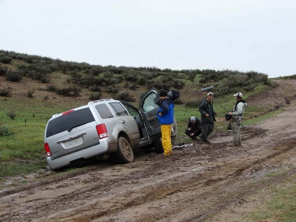 "Albert Villard and Jim Nicoletto hook a tow rope to the car of ""Dirty Jobs"" field producer Dave Barsky to pull it out of the mud as the ""Dirty Jobs"" film crew looks on."