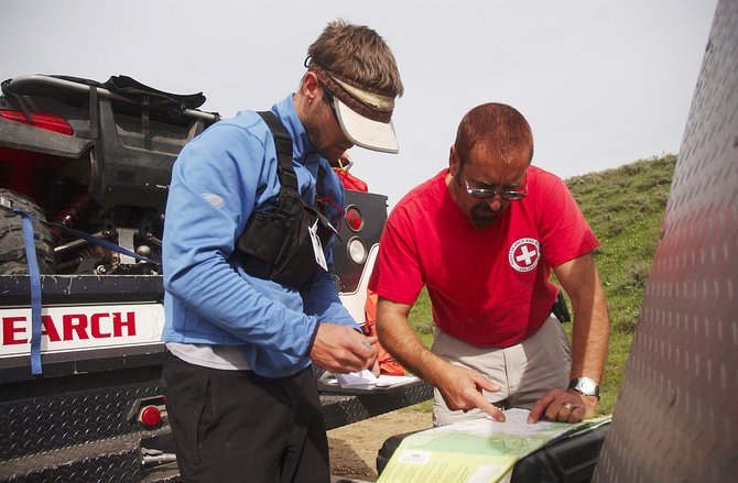 Routt County Search and Rescue President Darrel Levingston looks at a map with volunteer Patrick Meyer on Sunday at a staging area set up on Routt County Road 80 to look for a plane that went missing after taking off from Yampa Valley Regional Airport.