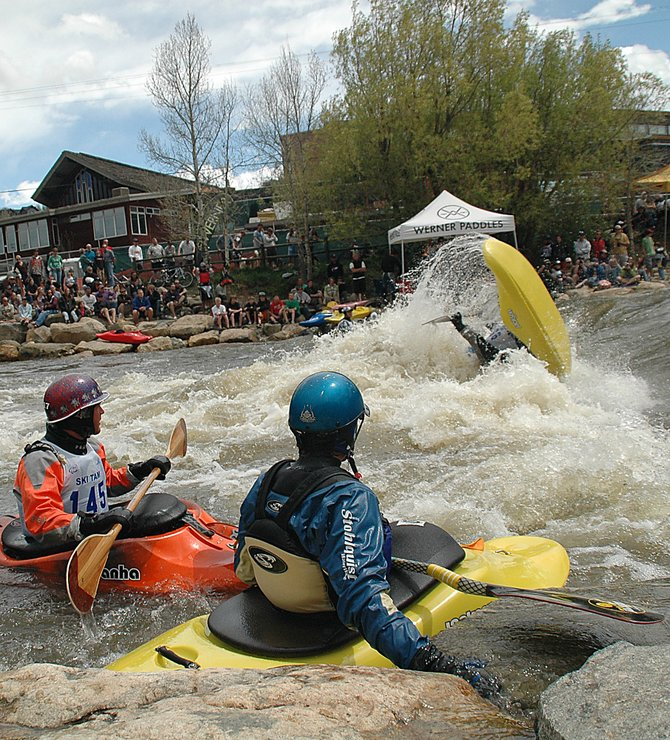 A large crowd, plus competitors Jeremy Laucks, left, and Jason Craig, watches Monday as Stephen Wright does a trick at Charlie's Hole on the Yampa River in downtown Steamboat Springs as part of the third annual Paddling Life Pro Invitational. The competition also involved a run down Fish Creek. Wright rode his second-place finish in the freestyle event to a third-place overall finish.