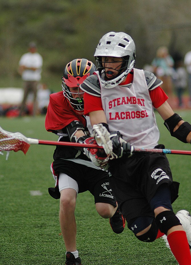 Steamboat Springs' Garrett Pugh tries to hang on to the ball while being checked by an opponent Sunday as the Steamboat eighth-grade lacrosse team beat the Panthers in the consolation game of the Steamboat Classic Lacrosse Tournament at Steamboat Springs High School.