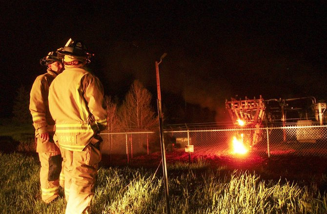 Firefighters stand by Sunday night as a fire burns at an electrical substation near the intersection of Walton Creek Road and U.S. Highway 40. An explosion at the substation caused a citywide power outage.