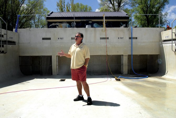 Dave Pike, city Parks and Recreation Department director, stands near the base of the wave pool in City Park, pointing out areas where crews applied aquapoxy to small cracks in the pool's surface. The damages to the pool are concerns, Pike said, but not immediate needs.