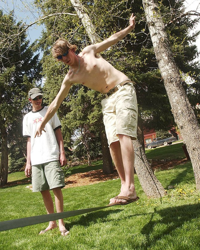 Drew Scharff adjusts his balance while slacklining Friday at Rich Weiss Park with his brother, Matt Scharff. The two were trying slacklining for the first time after purchasing 40 feet of webbing for about $20.